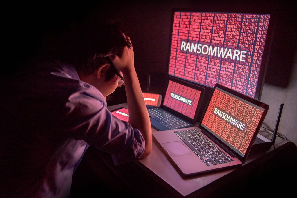 Young male frustrated by ransomware attack on desktop screen.